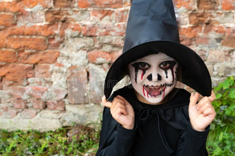 Scary little girl in a witch costume smiles against a brick wall. Happy Halloween royalty free stock photos