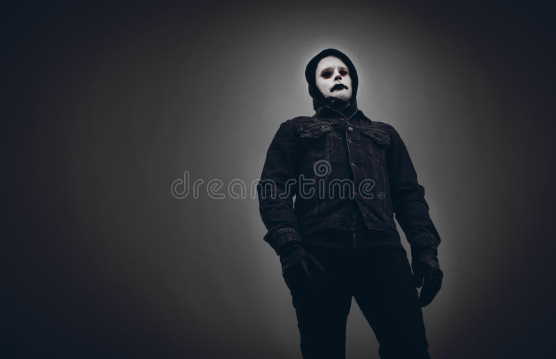 Scary looking, evil man in black hood. Creepy, deathlike, hooded man looking down at the observer. Face painted white. Dark, dull background stock images
