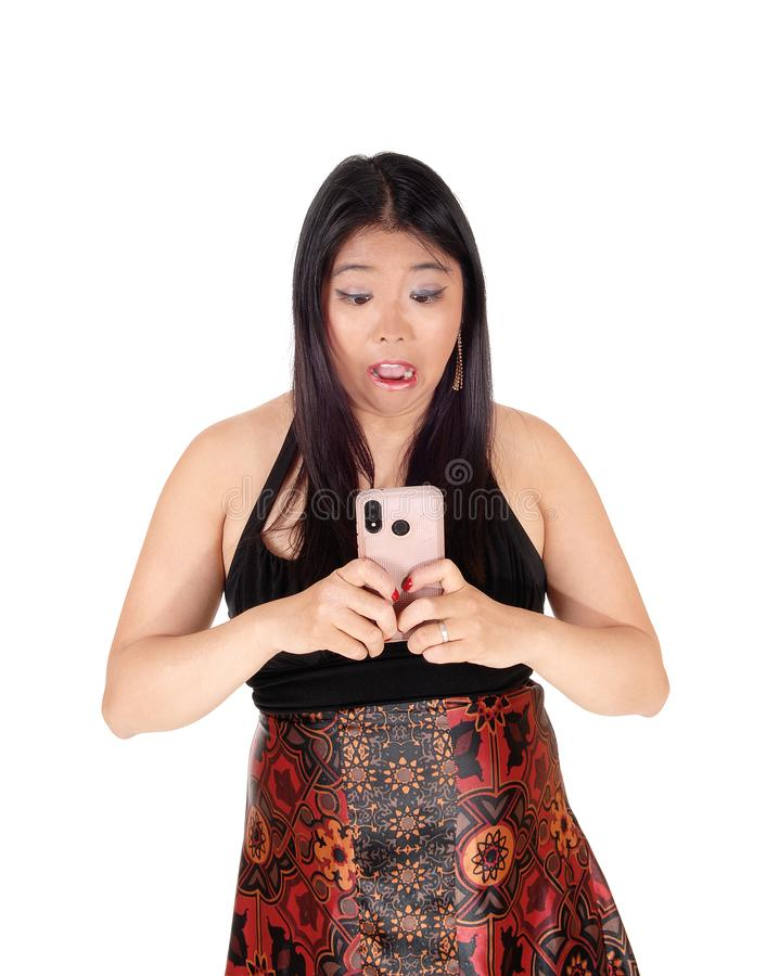 Scary  looking woman got a shocking message on cellphone royalty free stock photography