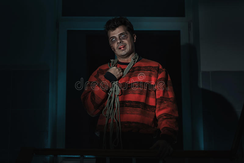 Scary man with a knife. Scary man killer with a knife in the room stock photography