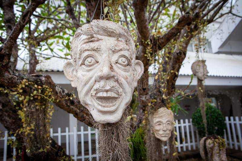 Scary masks hanging on trees at Wat Rong Khun - The White Temple - on a cloudy day. Chiang Rai royalty free stock photo