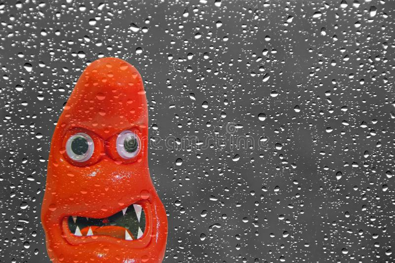 Scary monster face at rainy window. Concept photo of scary staring monster face peering through rainy window baring teeth stock photography