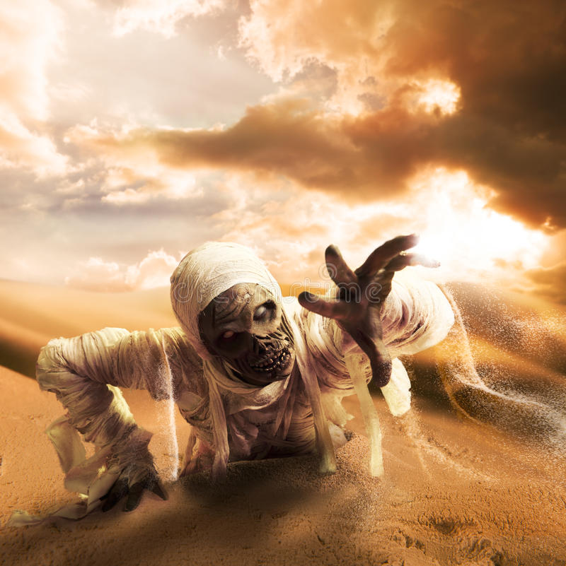 Scary mummy in a desert at sunset with copy space royalty free stock images
