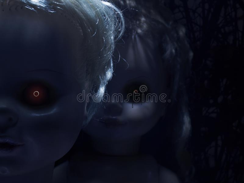 Scary plastic dolls with fiery eyes stock photography