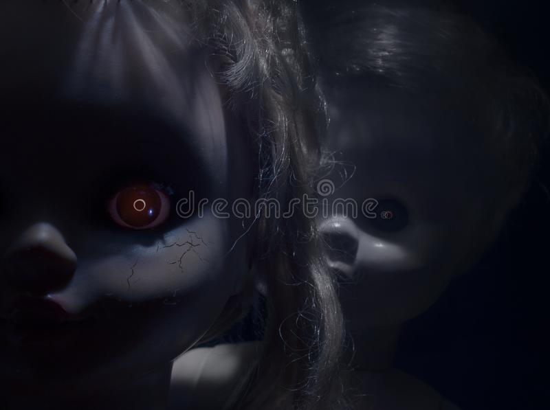 Scary plastic dolls with fiery eyes. Two creepy faces of scary plastic dolls with fiery eyes, closeup stock image