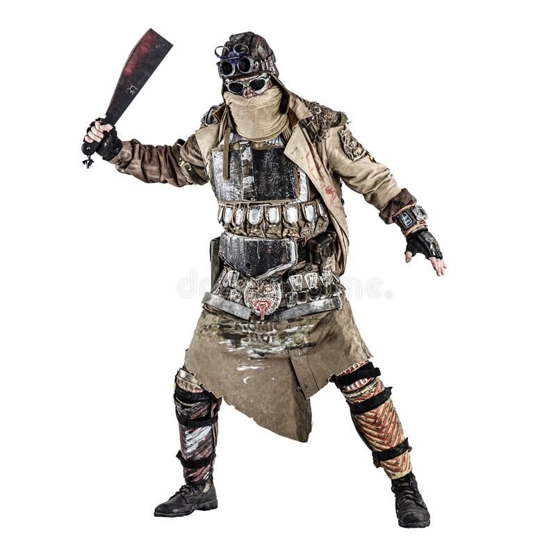 Terrifying post apocalyptic creature with machete. Scary post apocalyptic survivor in handmade armored clothes, armed with machete, dangerous creature with face royalty free stock photography