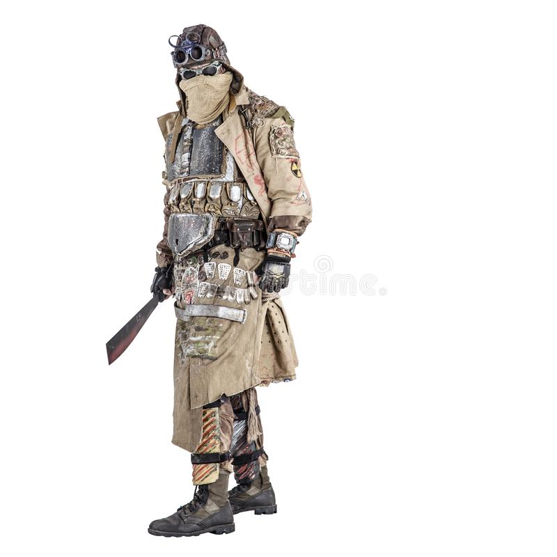 Terrifying post apocalyptic creature with machete. Scary post apocalyptic survivor in handmade armored clothes, armed with machete, dangerous creature with face royalty free stock photo