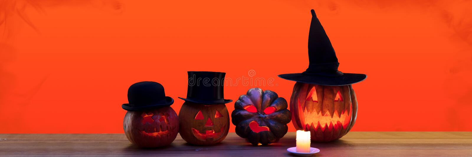 Scary pumpkins on black background, the night of fear. Scary pumpkins in hats on black background, the night of fear. Fire flames and candles. Halloween, black stock photo