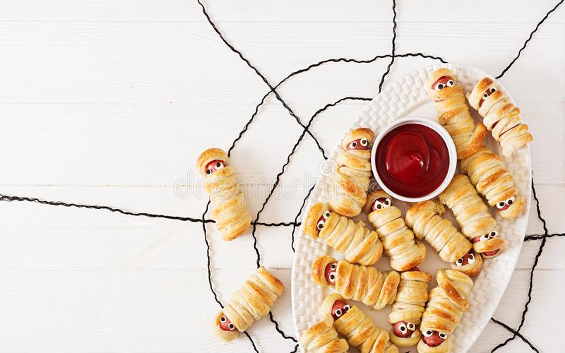 Scary sausage mummies in dough with funny eyes on table. royalty free stock images