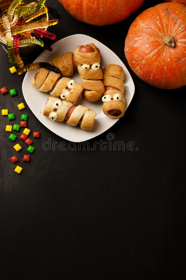 Scary sausage mummies in dough with funny eyes stock photo