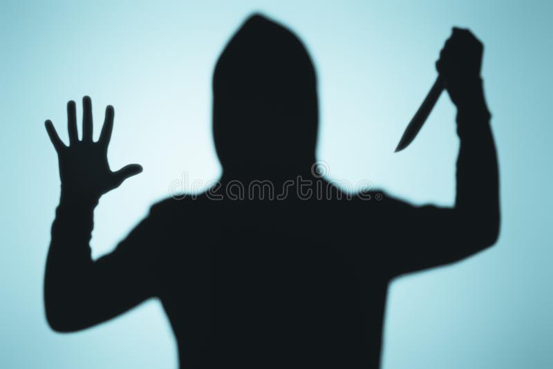 Scary shadow of person in hood holding knife. On blue royalty free stock photography