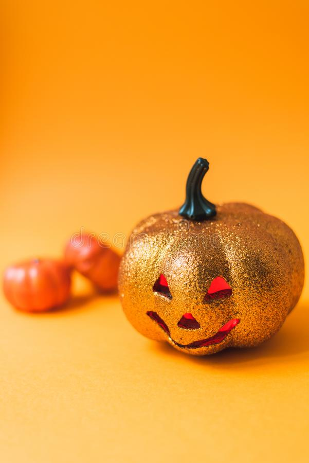 Scary shiny Halloween pumpkin toy. Jack-o`-lantern on an orange background with red luminous eyes with a place for text.  stock photography