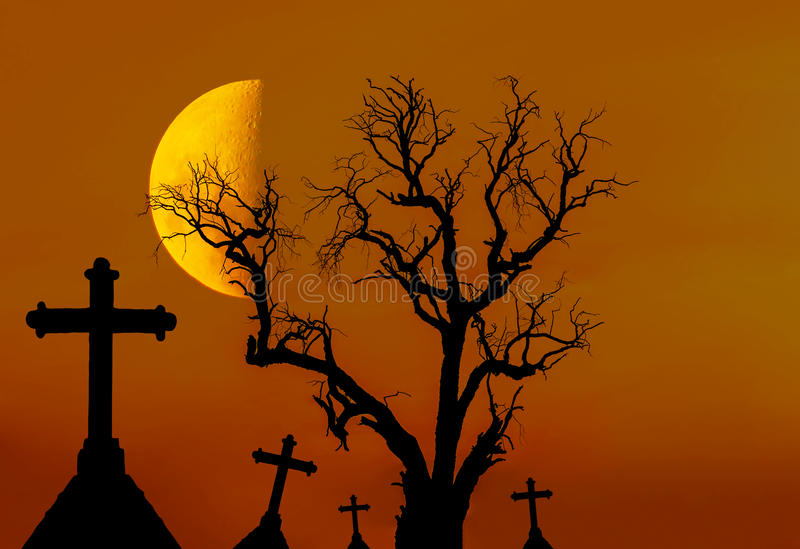 Scary silhouette dead tree and spooky silhouette crosses in mystic graveyard with half moon. In Halloween concept background royalty free stock image