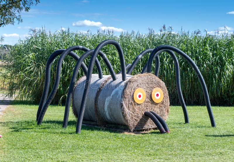 Scary spider made of round hay bales and plastic pipe royalty free stock photo