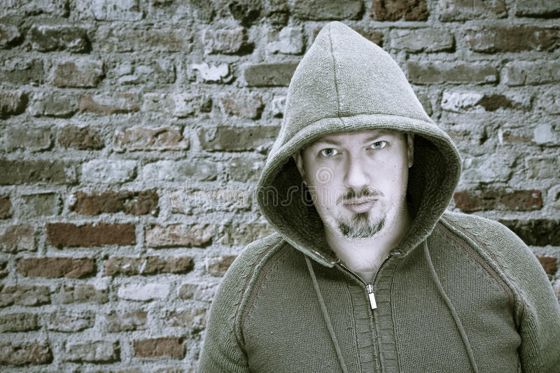 Scary stalker. An urban rapper hip hop guy in a hood against a brick wall royalty free stock images