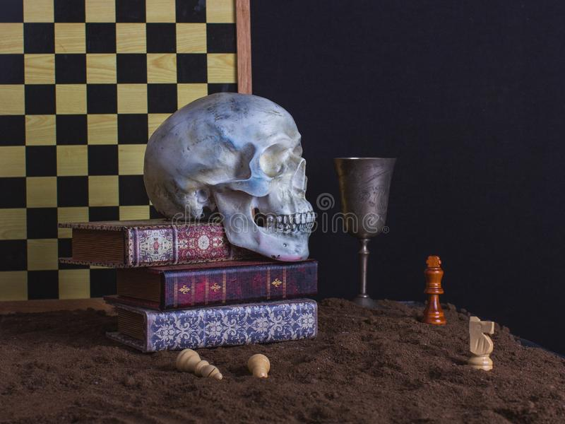 Scary still life with skull, chess, books and goblet of wine on royalty free stock photo