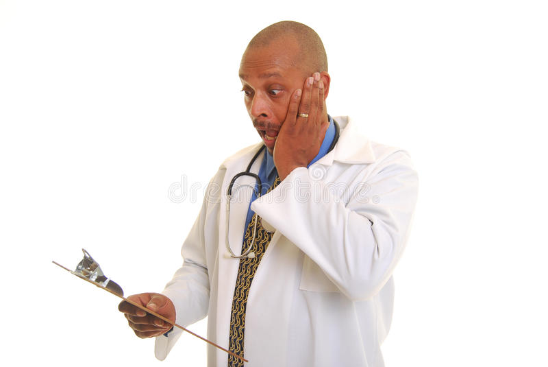 Scary test results. Sweating African American doctor shocked and scared by information on a clipboard stock photo