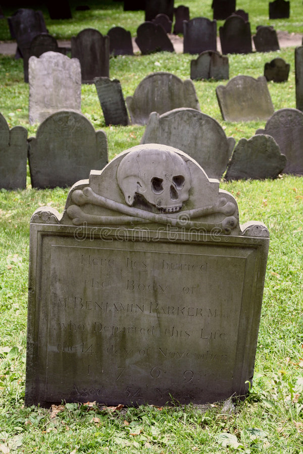Scary Tombstone. A tombstone in a colonial graveyard with a skeleton face and cross bones royalty free stock image