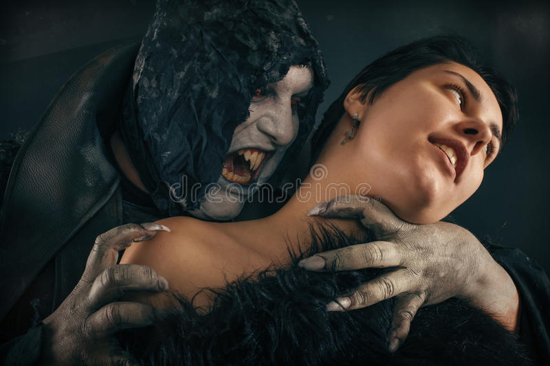 Scary vampire devil biting young woman. Medieval gothic nightmare horror. royalty free stock photo