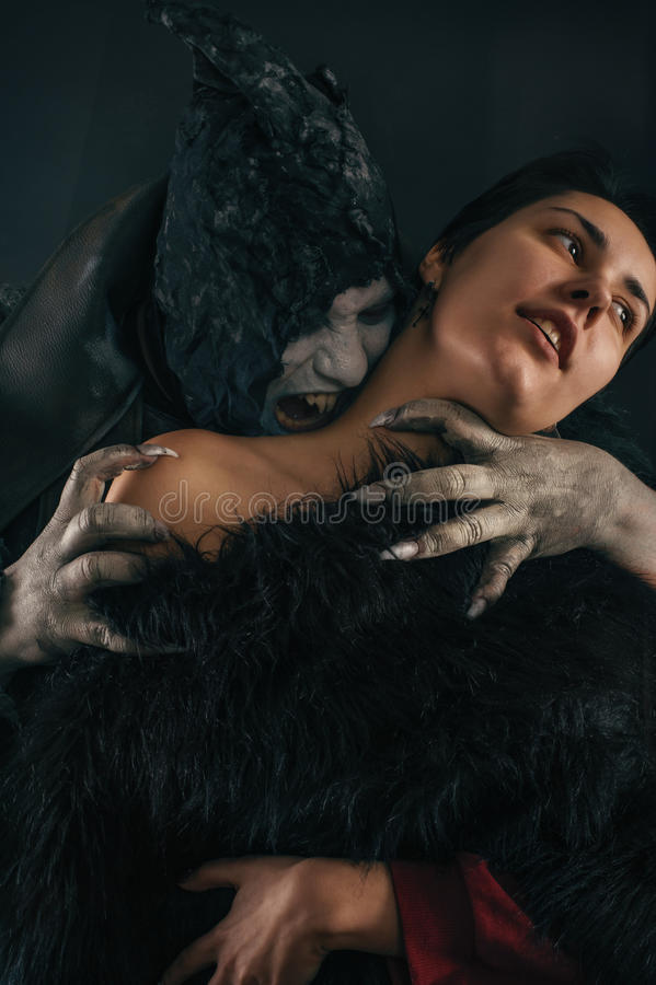 Scary vampire devil biting young woman. Medieval gothic nightmare horror. stock photos