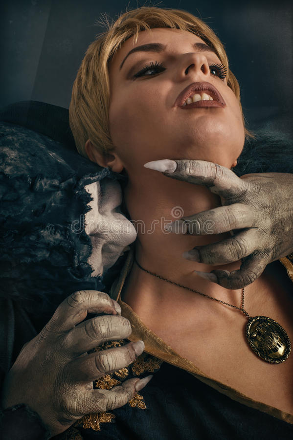 Scary vampire devil biting young woman. Medieval gothic nightmare horror. royalty free stock photos