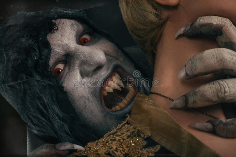 Scary vampire devil biting young woman. Medieval gothic nightmare horror. royalty free stock photography
