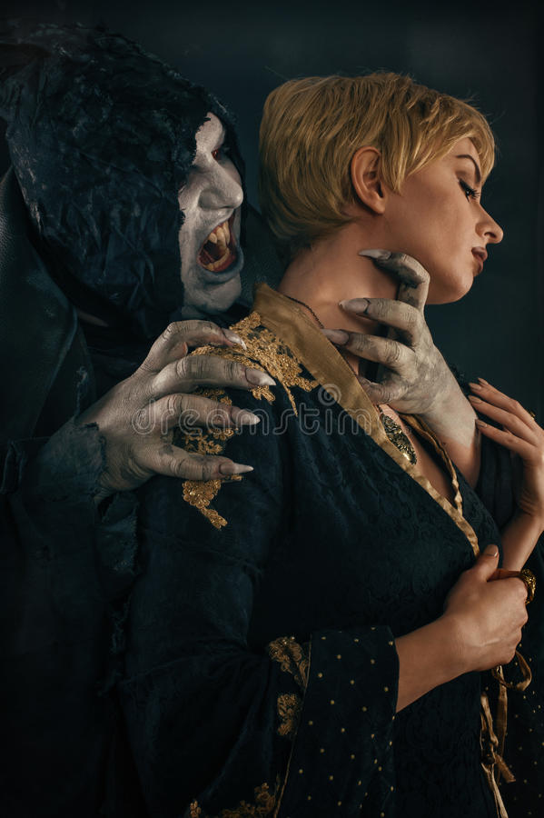 Scary vampire devil biting young woman. Medieval gothic nightmare horror. royalty free stock image