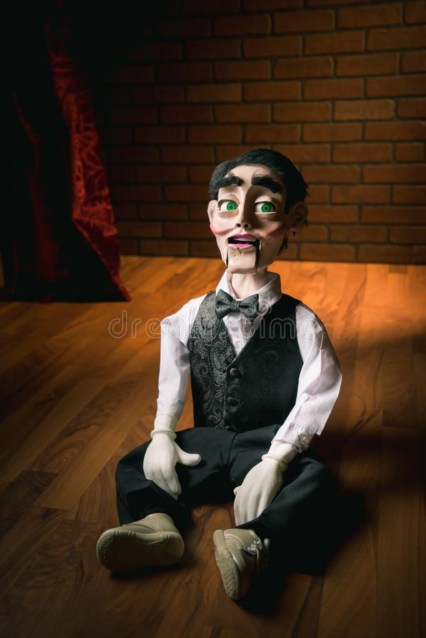 Scary ventriloquist doll sitting on the floor royalty free stock photography