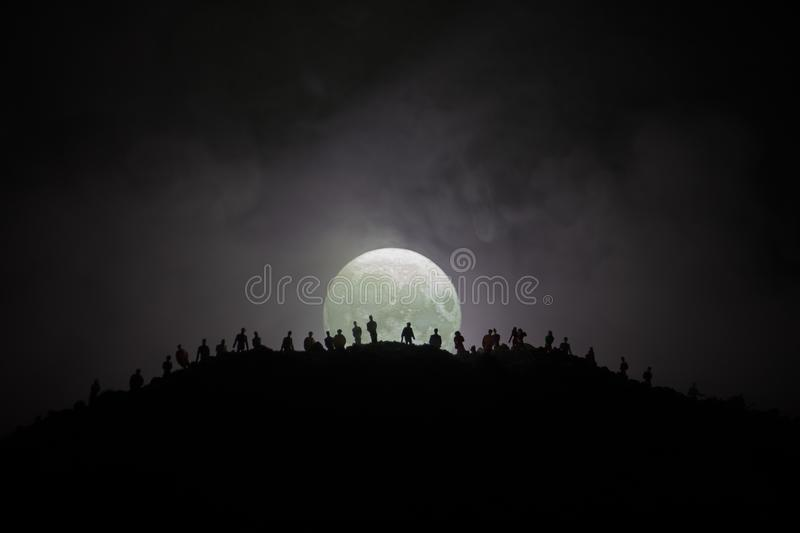 Scary view crowd of zombies on hill with spooky cloudy sky with fog and rising full moon. Silhouette group of zombie walking under. Full moon. Halloween concept vector illustration