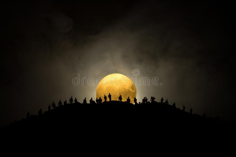 Scary view crowd of zombies on hill with spooky cloudy sky with fog and rising full moon. Silhouette group of zombie walking under royalty free stock photography
