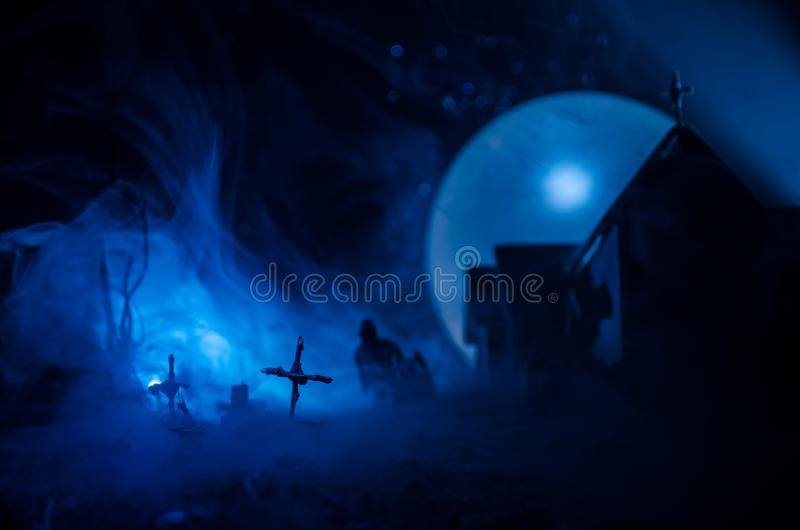 Scary view of zombies at cemetery dead tree, moon, church and spooky cloudy sky with fog, Horror Halloween concept. Toned stock image