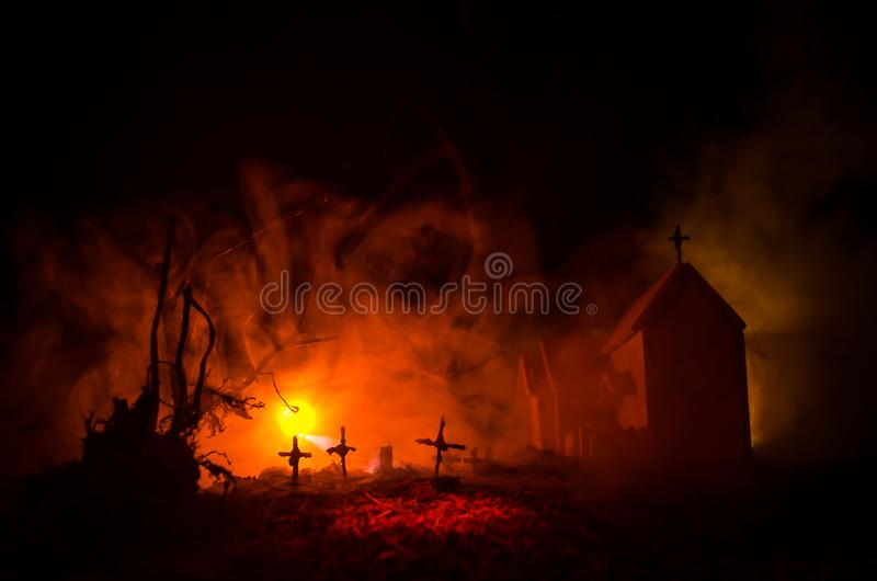 Scary view of zombies at cemetery dead tree, moon, church and spooky cloudy sky with fog, Horror Halloween concept. Toned royalty free stock photo