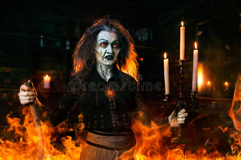 Scary witch with a cane at the mirror and candles. Dark powers of witchcraft, spiritual seance. Female foreteller calls the spirits, terrible fortune teller royalty free stock photos