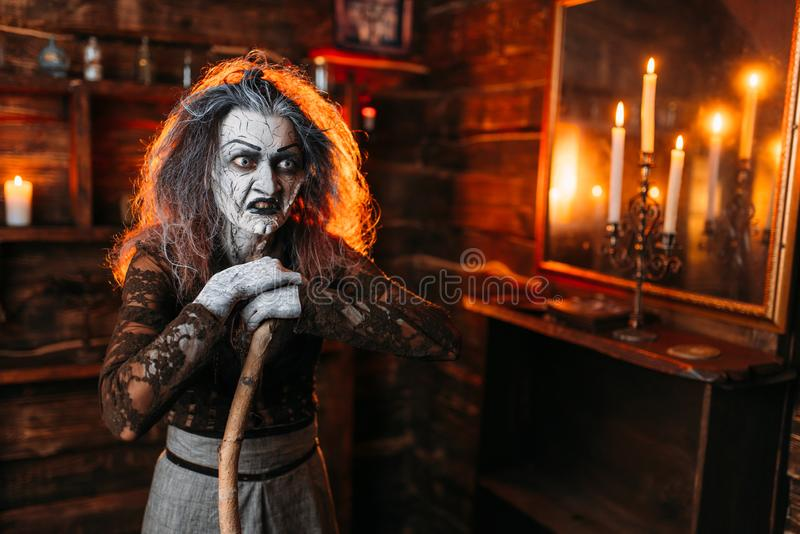 Scary witch with a cane at the mirror and candles. Dark powers of witchcraft, spiritual seance. Female foreteller calls the spirits, terrible fortune teller royalty free stock image