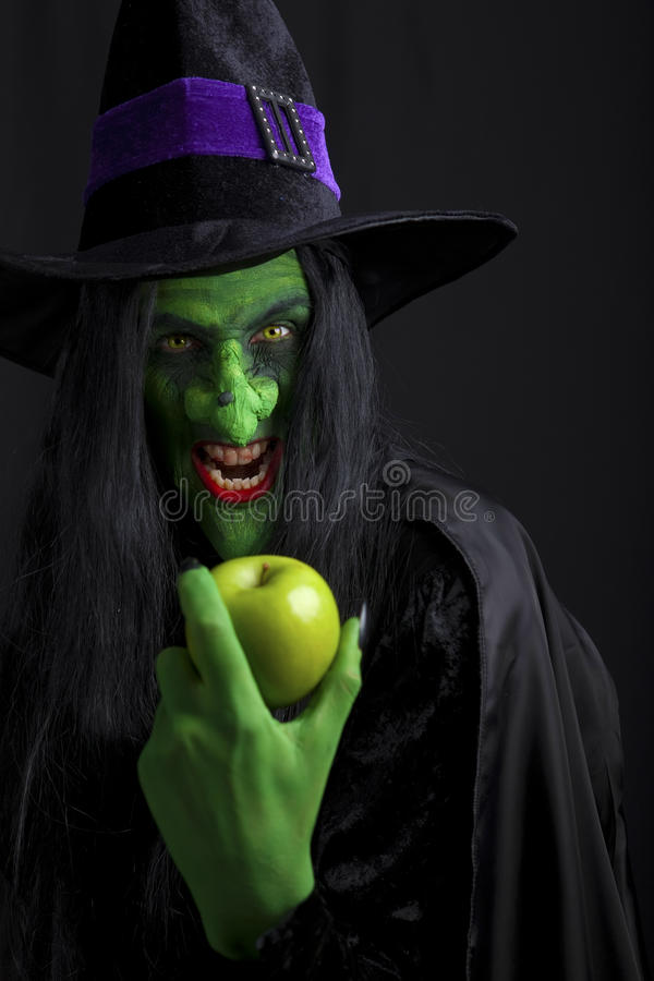 Scary witch holding an apple. stock photos