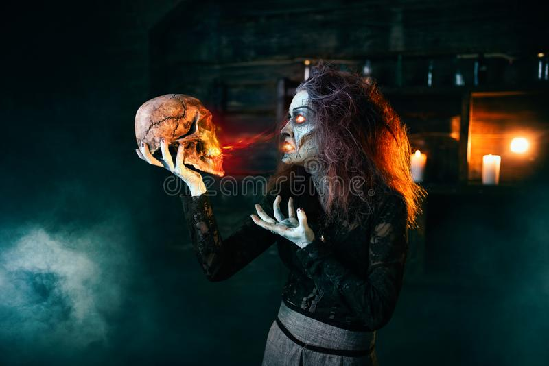 Scary witch holds human skull and reads the spell. Dark powers of witchcraft, spiritual seance. Female foreteller calls the spirits, terrible future teller stock images