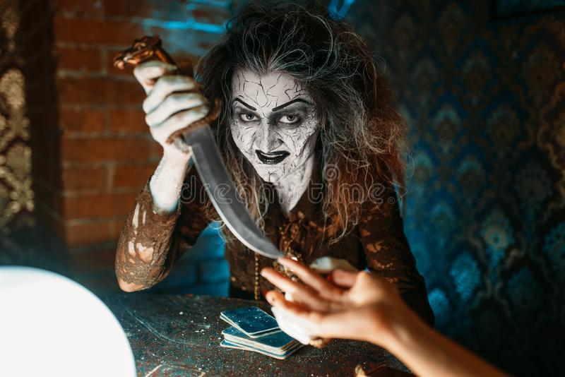 Scary witch with knife, spiritual seance. Scary witch with knife reads a magic spell over a crystal ball, young people on spiritual seance. Female foreteller royalty free stock photography