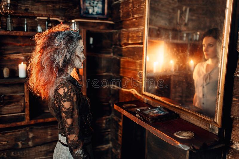 Witch at the mirror, young woman in the reflection. Scary witch at the mirror become young cute women in the reflection, spiritual seance. Female foreteller stock photography