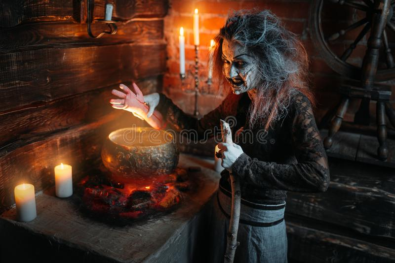 Scary witch reads spell over the pot, seance. Scary witch reads spell over the pot, dark powers of witchcraft, spiritual seance with candles. Female foreteller royalty free stock photo