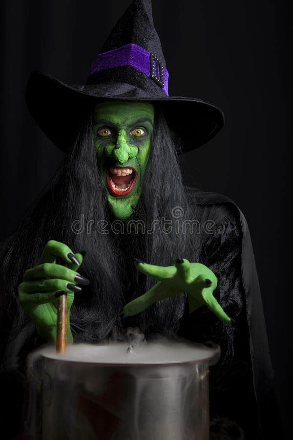 Scary witch stirring a cauldron royalty free stock photography