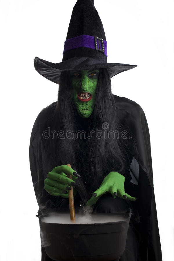 Scary witch stirring her cauldron stock photography