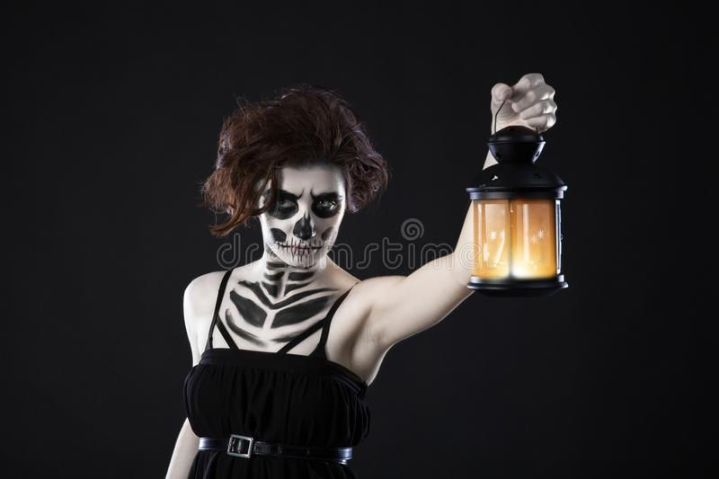 Scary woman with lantern over black background - Spooky image of a scary woman with dark eyes and appearance of a witch, in a whit royalty free stock image