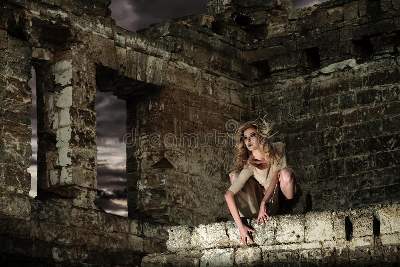 Scary woman in the ruins. Fantasy style portrait of the scary woman sitting on the ruined wall stock image