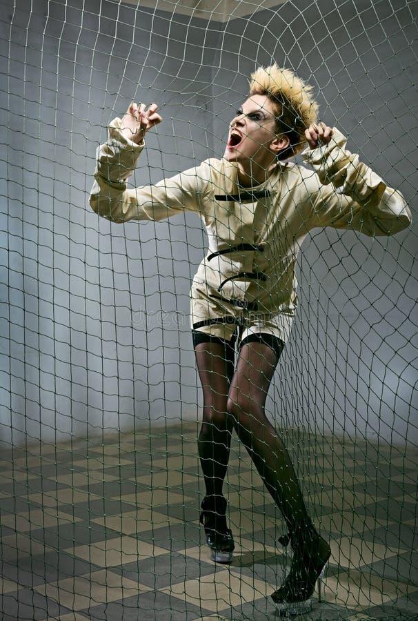 Scary zombie girl in gray room. In mental hospital stock image