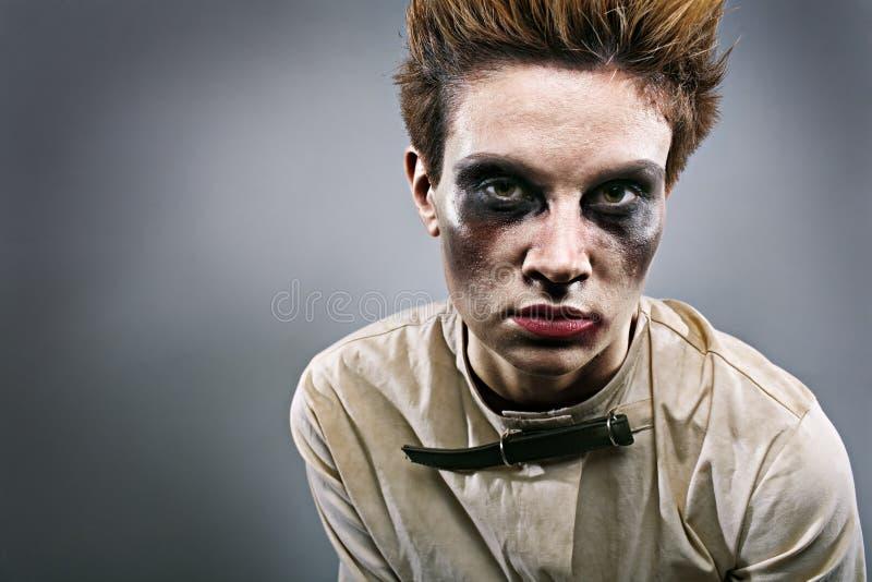 Scary zombie girl in gray room. In mental hospital stock photo