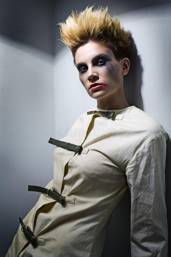 Scary zombie girl in gray room. In mental hospital royalty free stock photo