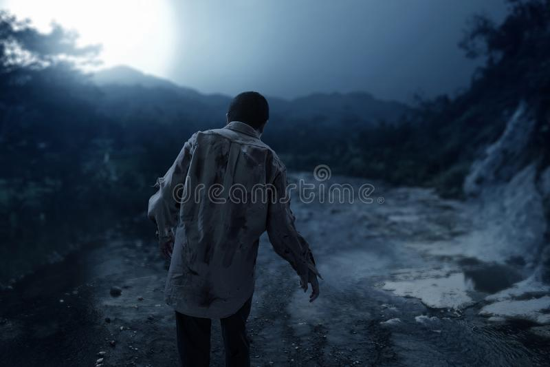 Scary zombie man walking at night stock photo