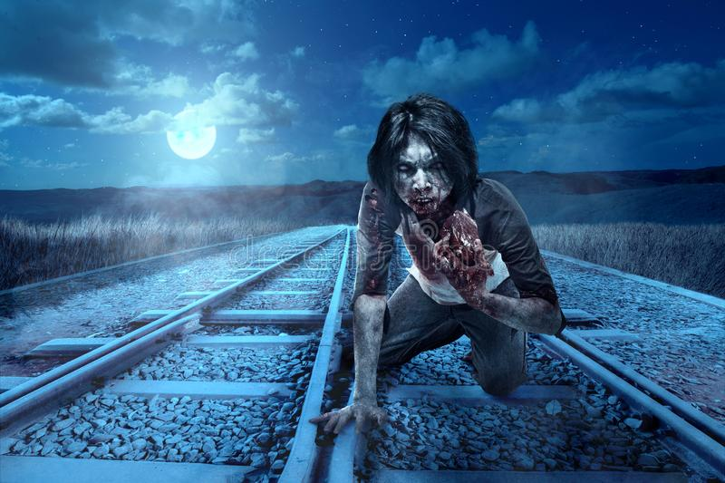 Scary zombies with blood and wound on his body eating the raw meat on the crossing of a railroad track. At night. Halloween concept royalty free stock images
