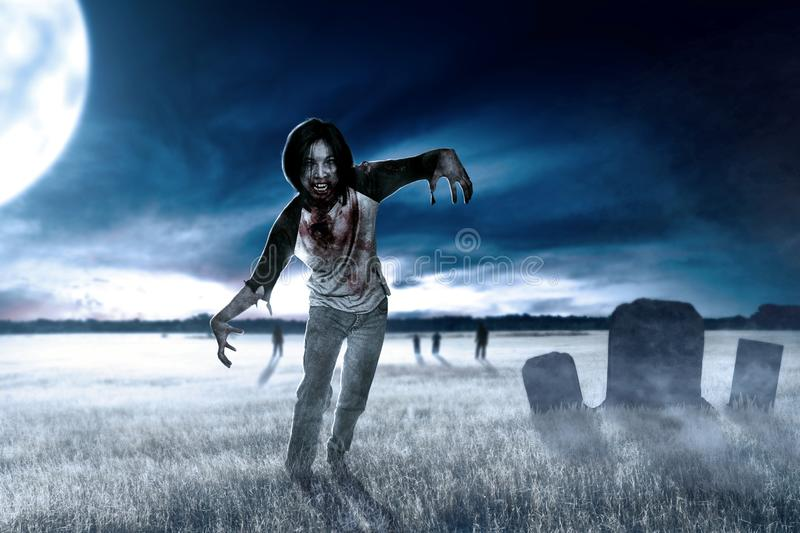 Scary zombies with blood and wound on his body walking around on the grass field. With a tombstone and moonlight. Halloween concept royalty free stock image
