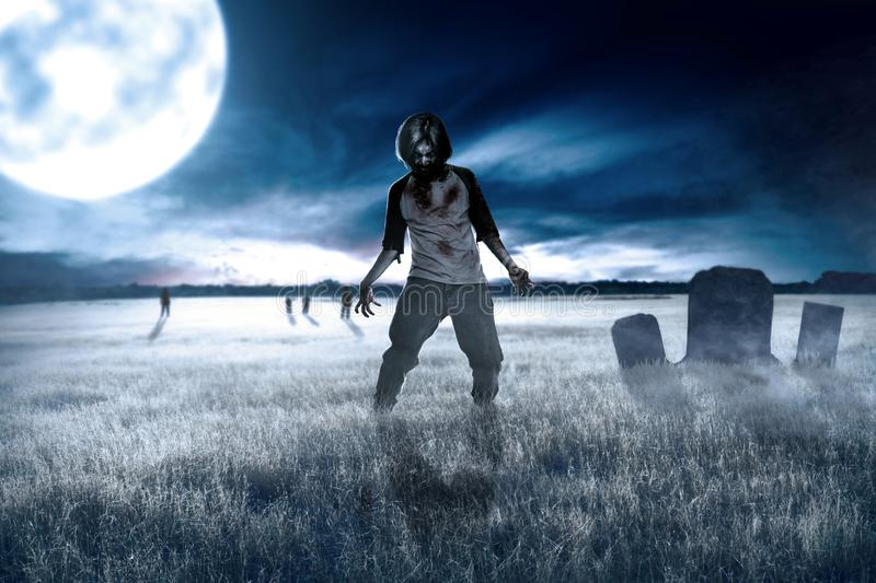 Scary zombies with blood and wound on his body walking around on the grass field. With a tombstone and moonlight. Halloween concept stock photos